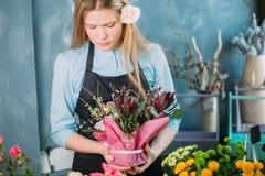 Displasing blommor för ung blomsterhandlare på blå bakgrund Fotografering för Bildbyråer
