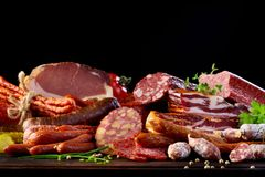 Display of assorted spicy sausages, salami and ham. Display of assorted spicy beef and pork sausages, salami, bacon and ham garnished with parsley, chives and royalty free stock photography