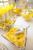 Display of candies. Display of yellow and white candies in glass jars and bowls during the reception party of a wedding stock photos