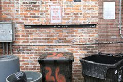 City Back Alley with Garbage Cans Close Up. A display of a close up shot of a city back alley behind a pub, showing the tops of garbage cans with a unique brick stock photography