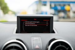 Display at a dashboard in a car with blurred background. Royalty Free Stock Image
