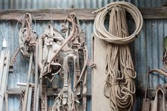 Workshop with display of dust farm equipment, ropes and tools hung against a corrugated iron wall stock images