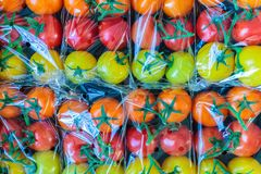 Display of fresh plastic wrapped cherry tomatoes. Display of fresh plastic wrapped yellow, orange and red cherry tomatoes stock image