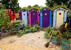 Garden display of colourfully painted beach huts. Royalty Free Stock Photography