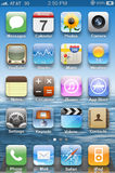 Display on iPhone 4s. Colorful application icons on main display on iPhone 4s Royalty Free Stock Photos