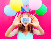 Display of phone woman in a birthday cap is taking a picture on a smartphone with an air colorful balloons on pink background Royalty Free Stock Images