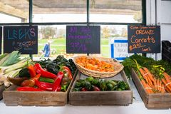 Display of Produce for Sale in Old Farmers Roadside Stand. Display of Leeks, Hot Peppers, and Organic Carrots with Signs with Prices in Old Farm Roade Stand royalty free stock image