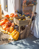 Display of pumpkins against farm house wall with two brooms and Stock Photo