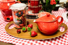 Display of red kitchenware in a store. Display of red kitchenware and ceramics in a store with a teapot, fondue, and assorted fresh berries in a container on a Stock Images