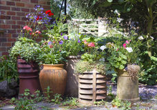 Display of reused chimney pots and pots in bloom stock photography