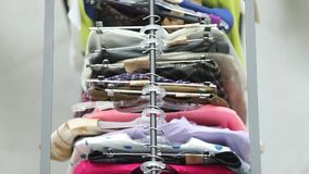 Sale of clothes on hangers among people from above stock footage