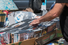 Display stand used DVD. Saint Hilaire de Riez, France - July 31, 2016 : a man looks for in a used DVD stand for a outdoor flea market Royalty Free Stock Photography