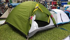 Display of tents for camping outdoor. Green and white tents are in display in a store for sell, various in sizes bin=g and small, nylon material, recreational royalty free stock image