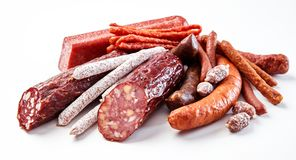 Display of a variety of seasoned spicy sausages. Display of a variety of seasoned spicy and smoked sausages with some cut through to show the texture of the meat Stock Image
