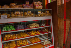 Display window of a bakery and pastry shop of with variety of baked goods, breads, donuts, puff pastry, closeup. Philippines. Stock Image