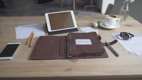 Display of work table desktop with tablet cell phone watch cup of hot coffee tea drink and leather case note pad journal. Display of work table desktop with stock footage