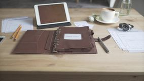 Display of working space area desktop wooden table with tablet cell phone watch cup of hot drink keather case note pad. Close up shot of elegant light brown stock video footage