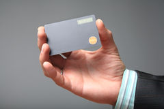 Displaycard Token. With the button and one-time password on screen in the hands of a businessman. Grey background Stock Photos