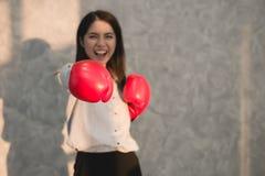 Displayin rojo de la mano de los guantes de boxeo del hombre de negocios asiático de las muchachas que lleva Fotos de archivo