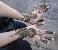 Displaying a Henna Tattoo. A delicate deft touch is used to inscribe the design to a henna tattoo on the arm of a young female tourist in Meknes, Morocco. The stock images