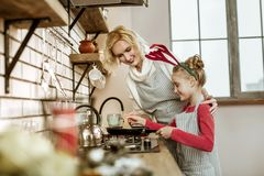 Smiling blonde mother and her beaming daughter standing nearby stock photo