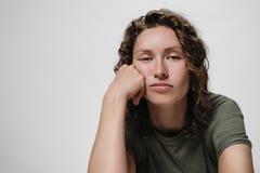 Displeased утомляло сонную курчавую женщину, подпирающ его щеку, смотря пробурено стоковые фото