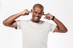 Displeased african man closes ears from a noise. Image of young displeased african man standing isolated over white background closes ears from a noise royalty free stock photos