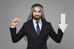 Displeased arabian muslim businessman in keffiyeh kafiya ring igal agal black suit isolated on gray background