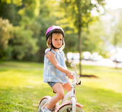 Displeased baby girl with bicycle in park Royalty Free Stock Photos