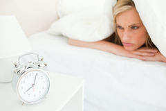 Displeased blonde woman waking up Royalty Free Stock Images