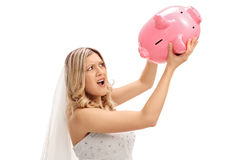 Displeased bride shaking an empty piggybank Royalty Free Stock Images