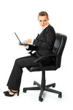 Displeased business woman holding laptop in hand. Displeased modern business woman sitting on chair and holding laptop in hand isolated on white stock images