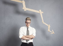 Displeased businessman in front of graph with negative trend. Stock Photography