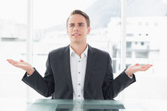 Displeased businessman with hand gesture at office desk Royalty Free Stock Images