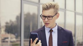 Displeased businessman having unpleasant online video chat. Male expressing his irritation. Angry Man Using Smartphone. stock video footage