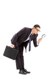 Displeased businessman looking through a magnifier Stock Photography
