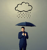 Displeased businessman with umbrella. Standing under drawing storm cloud over dark background Royalty Free Stock Photography