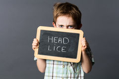 Displeased child hiding behind a school slate scaring head lice Royalty Free Stock Images