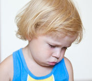 Displeased child with pouty lips. Kid with guilty sulky look, isolated on white Stock Images
