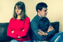 Displeased couple sitting back to back on couch. In living room Royalty Free Stock Photo