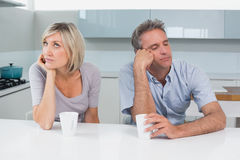 Displeased couple sitting with coffee cups in kitchen Royalty Free Stock Photos