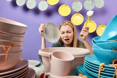 Displeased emotional depressed frustrated housewife drying dishes. Displeased emotional depressed frustrated housewife washing dishes. close up portrait, clen royalty free stock photo