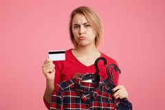 Displeased female shopaholic takes variety of clothes on hangers, holds plastic card in hands, has unhappy look as being short of. Money, can`t buy new outfit stock photo