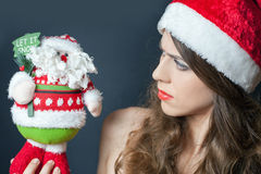 Displeased frown dressed in red hat looking at Santa Claus Royalty Free Stock Photo