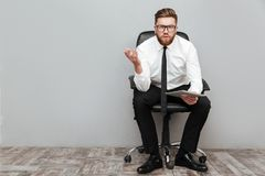 Displeased frustrated businessman in eyeglasses holding pc tablet. While sitting in chair and gesturing with hand isolated over gray background stock photos