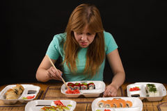 Displeased girl chooses from a plate with ginger rolls Royalty Free Stock Images