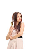 Displeased girl looking at something. And holding a glass of wine isolated on white background Royalty Free Stock Photography