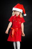 Displeased girl in red dress and santa cap Royalty Free Stock Photo