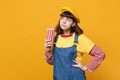Displeased girl teenager in french beret denim sundress holding plastic cup of cola or soda on yellow wall. Background in studio. People sincere emotions stock photo