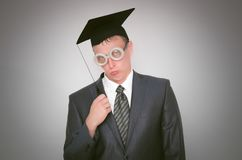 Graduate student. Displeased graduate student in the cap isolated on gray background. Education concept royalty free stock image
